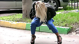 Blonde girl on high heel shoes releases piss in her pants